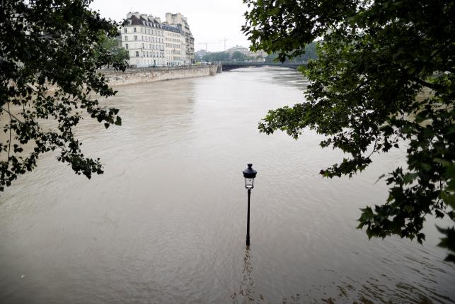 The waters of the Seine River flow out of its banks at the tip of the Ile Saint Louis after days of rainy weather in Paris