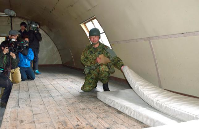 A member of JGSDF shows the mattress which a 7-year-old boy who went missing on May 28, 2016 after being left behind by his parents, was found alive, used inside a building at JGSDF's Komagatake exercise area, in Shikabe town