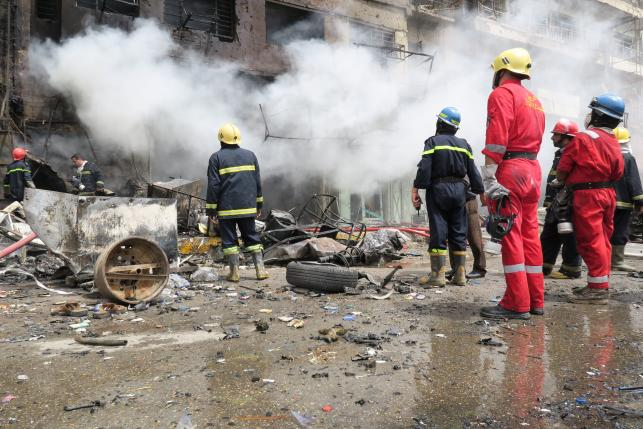 Firemen look at smoke from a burning building at the site of a car bomb attack in Baghdad al-Jadeeda