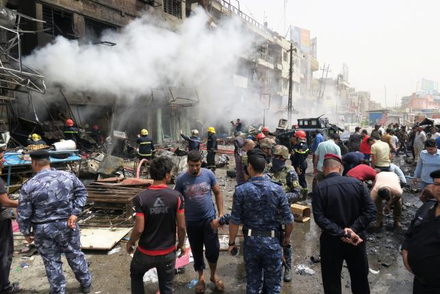Smoke rises from a burning building at the site of a car bomb attack in Baghdad al-Jadeeda