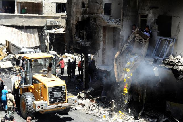 Men remove debris from a damaged site after a suicide and car bomb attack in south Damascus Shi'ite suburb of Sayeda Zeinab