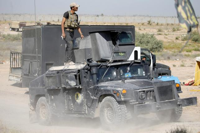 A member of the Iraqi security forces ride atop a military vehicle near Falluja