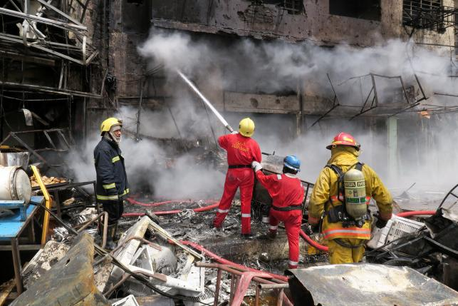 Firemen hose down a burning building at the site of car bomb attack in Baghdad al-Jadeeda