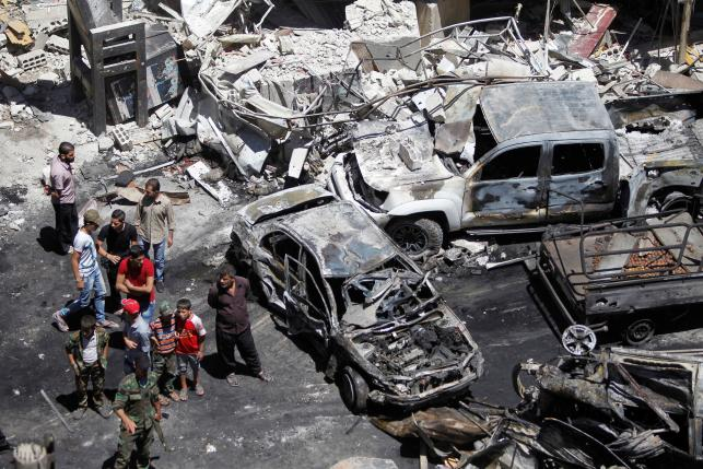People and Syrian Army members inspect a damaged site after a suicide and car bomb attack in south Damascus Shi'ite suburb of Sayeda Zeinab