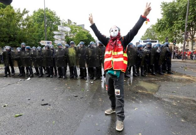 A masked youth faces off with French riot police during a demonstration in Paris as part of nationwide protests against plans to reform French labour laws