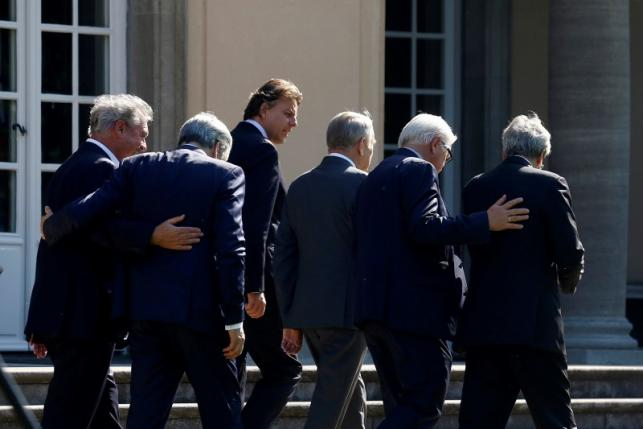 Ministers walk through the Park of the German Foreign Ministery guest house before a foreign minister meeting of the EU founding members in Berlin