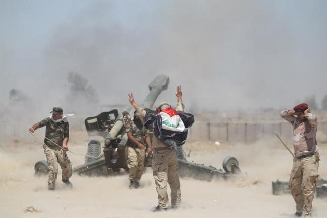 Shi'ite fighters and Iraqi security forces fire artillery during clashes with Islamic State militants near Falluja