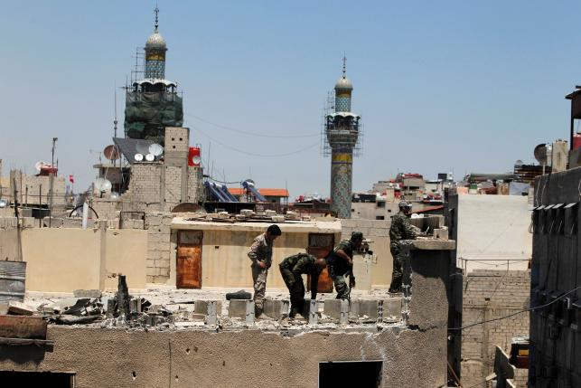 Syrian Army members inspect a damaged roof near Sayeda Zeinab mosque minarets after a suicide and car bomb attack in south Damascus Shi'ite suburb of Sayeda Zeinab