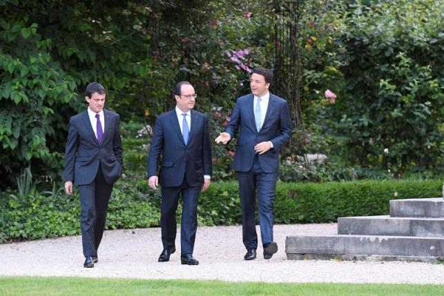 French Prime Minister Manuel Valls, French President Francois Hollande and Italy's Prime Minister Matteo Renzi walk in the gardens at the Elysee Palace in Paris