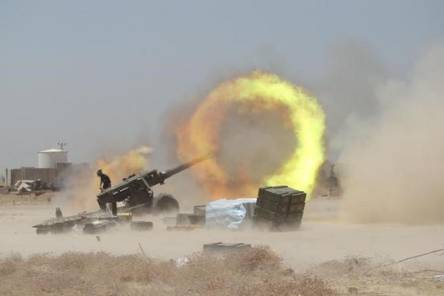 An Iraqi Shi'ite fighter fires artillery during clashes with Islamic State militants near Falluja