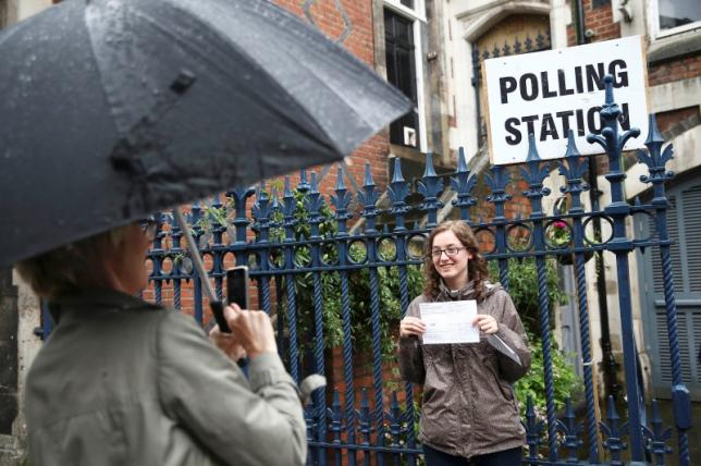 A woman photographs her daughter after she voted at a polling station for the Referendum on the European Union in north London