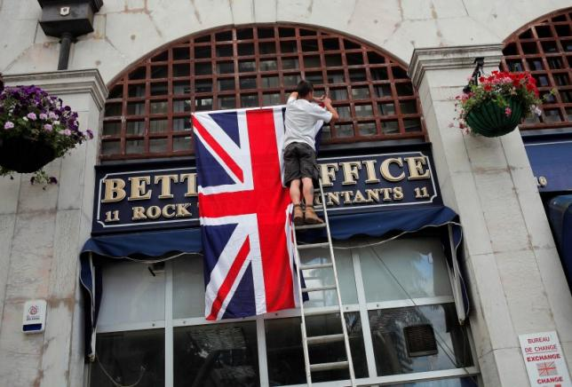 A worker places the Union Jack flag on the facade of a shop at Casesmates square where Cameron will attend a 'Stronger In' campaign event in the British overseas territory Gibraltar, historically claimed by Spain