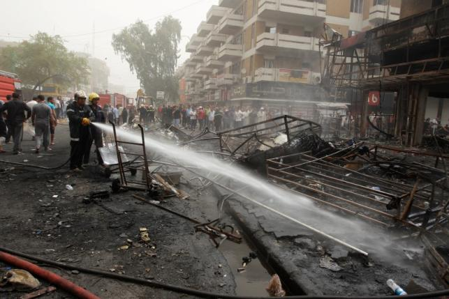Firemen hose down a burning building as civilians gather after a suicide car bomb occurred in the Karrada shopping area in Baghdad, Iraq