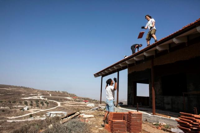 Men work on the roof of a house under construction in the unauthorised Jewish settler outpost of Havat Gilad, south of the West Bank city of Nablus