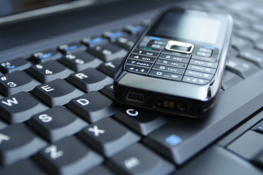 Mobile phone on laptop keyboard as a business concept