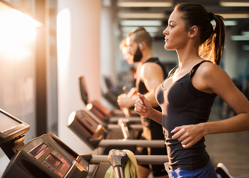People running on a treadmill in health club.