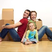 Happy family in their new home with cardboard boxes - moving concept